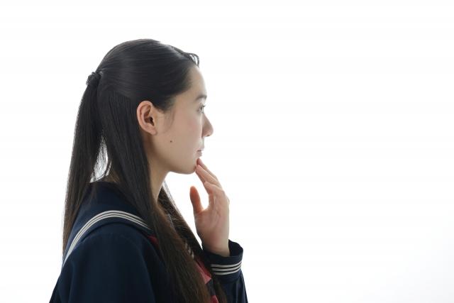 顎に手をやり顎を引く女性