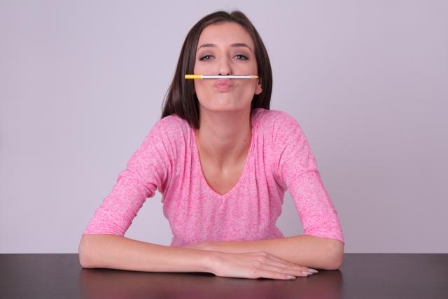 鼻と唇でペンを挟む女性