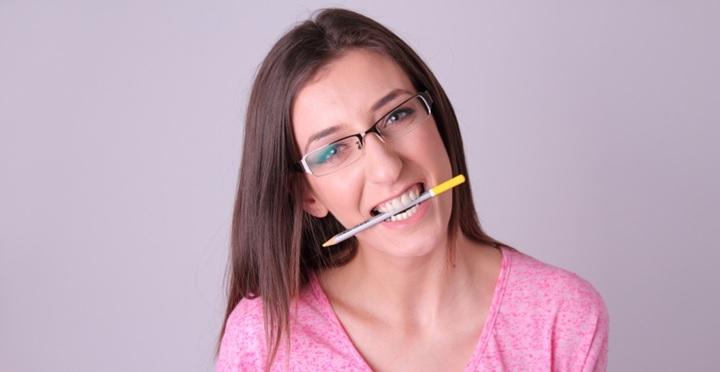 前歯でペンを噛む
