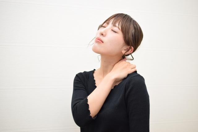肩こりや疲れを感じ肩に手を置く女性